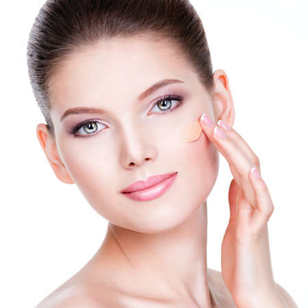 foundations: Beautiful face of young woman with cosmetic foundation on a skin over white background. Beauty treatment concept.