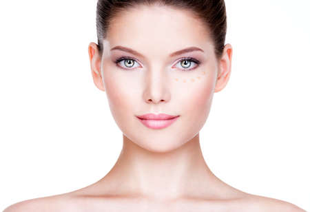 Beautiful young woman with cosmetic foundation on a skin. Beauty treatment concept.