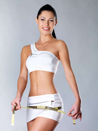 Smiling healthy woman after dieting measures hip. Healthy lifestyle. LANG_EVOIMAGES