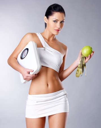 Healthy woman stands with the scales and green apple. Healthy eating concept. LANG_EVOIMAGES