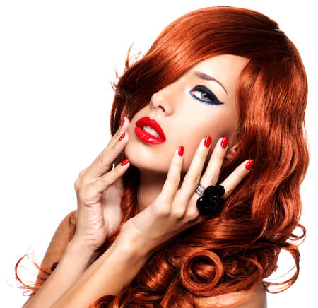 Beautiful sensual woman with long red hairs and red nails -  isolated on white. photo
