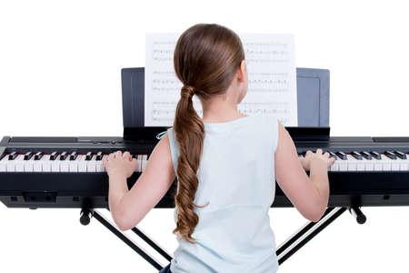 tocando piano: Volver la vista de una niña que juega el piano eléctrico - aislado en blanco. Foto de archivo
