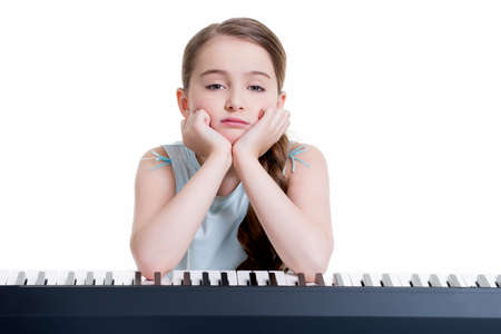 Cute serious little girl plays on the electric piano - isolated on white. Standard-Bild