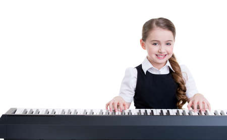 kid sitting: Cute happy smiling schoolgirl plays on the electric piano - isolated on white.