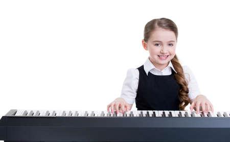 Nette glücklich lächelnde Schülerin spielt auf dem E-Piano - isoliert auf weiß.