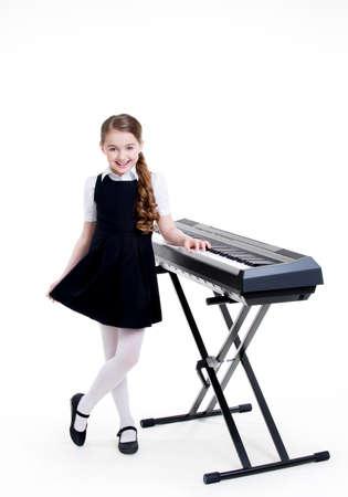 školačka: Portrét roztomilý usmívající se školačka stojící u elektrického klavíru - na bílém. Reklamní fotografie