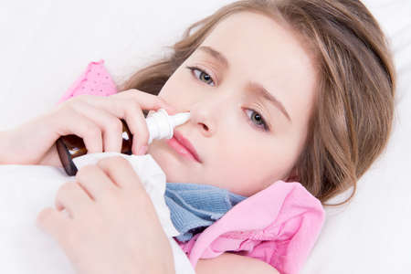 Little girl with bad cold lying in bed andusing nasal drops on white background.