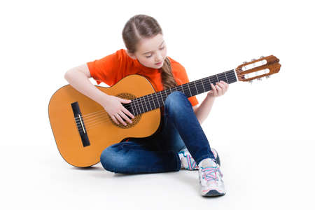 Cute girl sitting and plays on the acoustic guitar -  isolated on white background. Archivio Fotografico