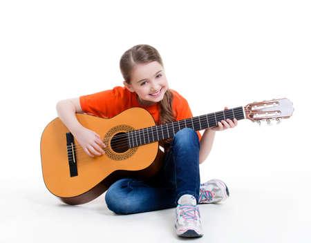 ni�os sentados: Linda ni�a juega en la guitarra ac�stica con emociones brillantes - aislados en fondo blanco. Foto de archivo