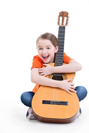 Chica linda que se sienta con la guitarra acústica con emociones brillantes - aislados sobre fondo blanco.