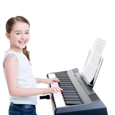 kid  playing: Cute happy smiling girl plays on the electric piano - isolated on white.