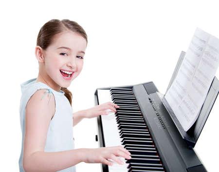 tocando piano: Linda chica sonriente feliz juega en el piano eléctrico - aislado en blanco.
