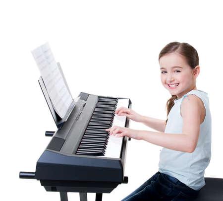 piano: Linda chica sonriente feliz juega en el piano eléctrico - aislado en blanco.