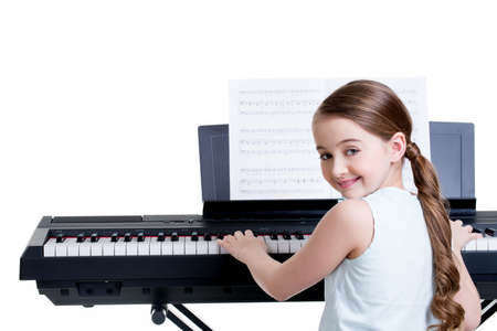 keyboard music: Cute happy smiling girl plays on the electric piano - isolated on white.