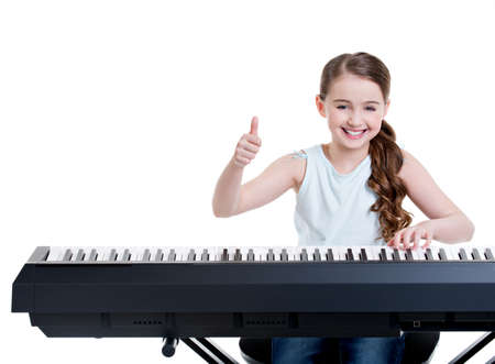 Cute happy smiling girl plays on the electric piano and shows thumbs up - isolated on white. Archivio Fotografico