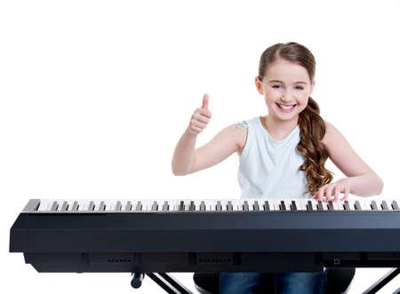 piano: Linda chica sonriente feliz juega en el piano el�ctrico y muestra los pulgares para arriba - aislados en blanco. Foto de archivo