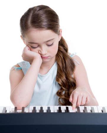 niños tristes: Linda niña grave juega en el piano eléctrico - aislado en blanco.