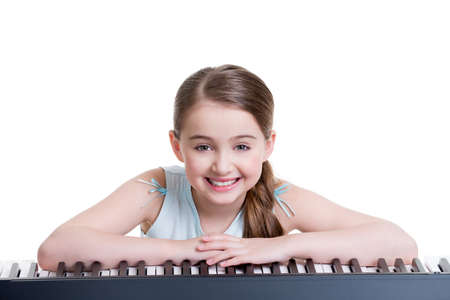 Cute happy smiling girl plays on the electric piano - isolated on white. photo