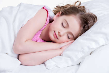 Adorable little girl in pink nightie sleeps in the bed on a white background.