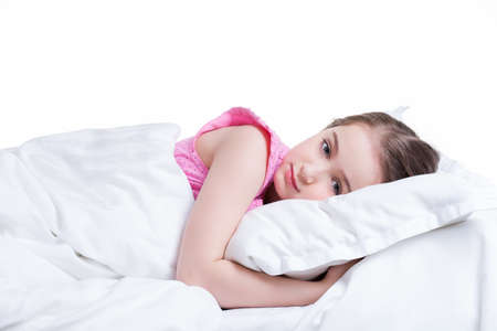 Adorable little girl in pink nightie awake in the bed on a white background. photo