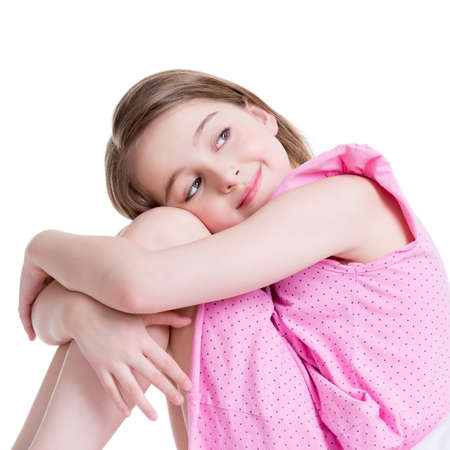 Adorable happy little girl sitting on the bed and looking up -  isolated on white. photo