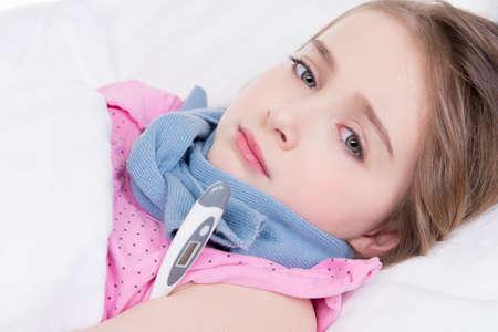 personne malade: Petite fille mignonne mesure la temp�rature sur un fond blanc.