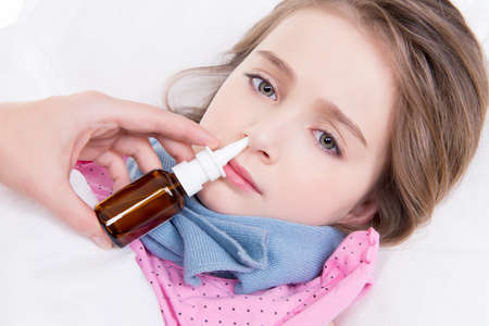 Little girl with bad cold lying in bed andusing nasal drops on white background. photo