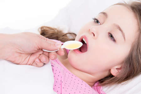 Little girl with sore throat lying in bed and using cough syrup on white background. photo