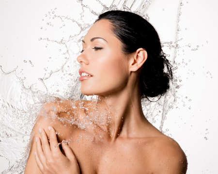Beautiful naked woman with wet body and splashes of water photo