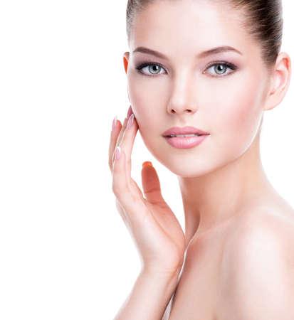 Belle jeune femme avec la peau fraîche et propre qui touche son visage avec une main - isolé sur blanc. LANG_EVOIMAGES