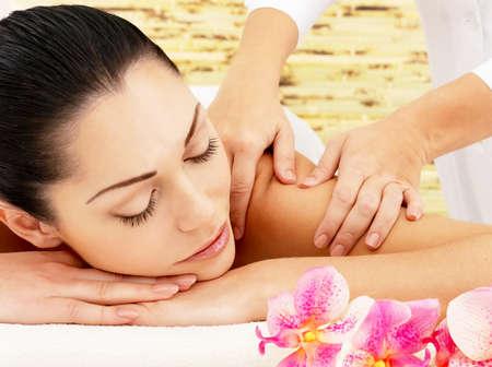 Mladá žena na lázeňské masáž ramene v salonu krásy.