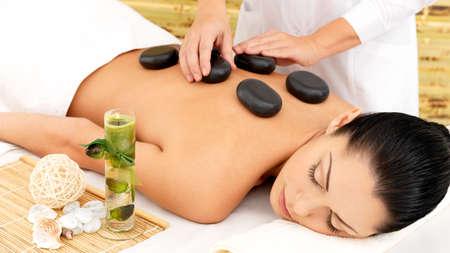Mujer que tiene masaje caliente de piedra spa de vuelta en el salón de belleza