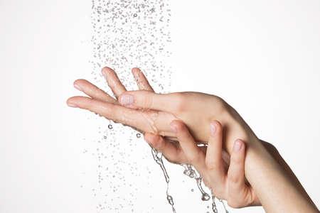 puro: Primer manos femeninas bajo el chorro de agua que salpica - concepto de cuidado de la piel