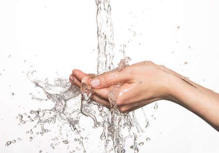 agua: Primer manos femeninas bajo el chorro de agua que salpica - concepto de cuidado de la piel