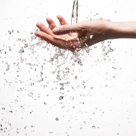 Closeup woman hand under the stream of splashing water - skin care concept Stock Photo