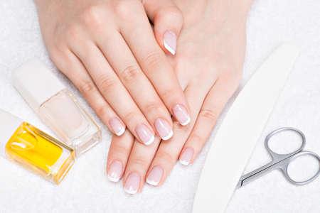 Frau in ein Nagelstudio erhalten Maniküre durch eine Kosmetikerin. Schönheitspflege-Konzept.