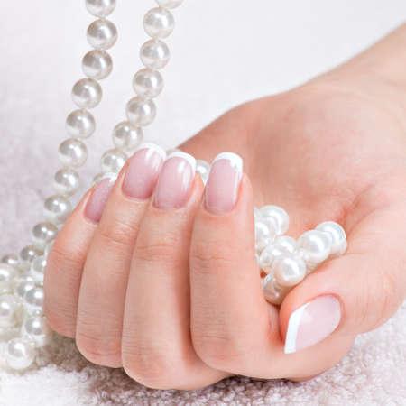 Les ongles de belle femme avec belle manucure française et de perles blanches