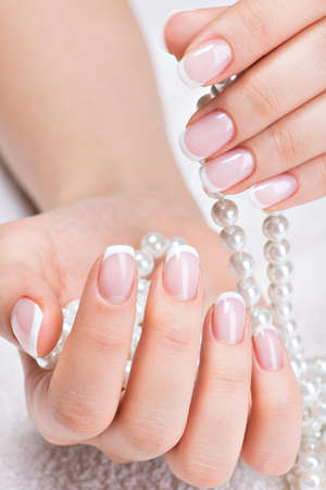 Beautiful woman's nails with beautiful french manicure  and white pearls