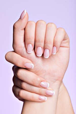Le mani della bella donna con belle unghie dopo salone manicure con french manicure Archivio Fotografico - 34216175
