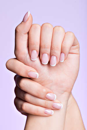 Les mains belle femme avec de beaux ongles après salon de manucure avec manucure française Banque d'images