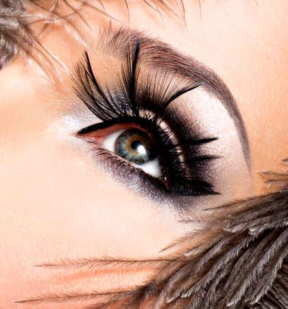 Mujer hermosa con brillante maquillaje profesional con plumas cerca de la cara.