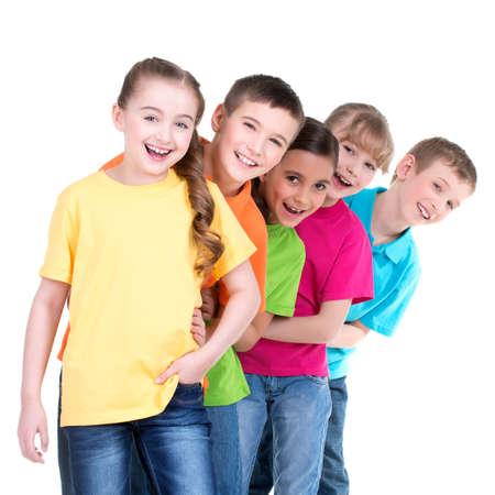 Gruppe glückliche Kinder in bunten T-Shirts stehen hintereinander auf weißem Hintergrund.