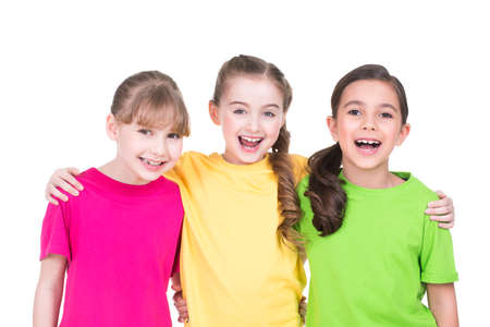 Three cute little cute smiling girls in colorful t-shirts standing -  isolated on white.