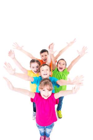 Gruppe lächelnde Kinder mit erhobenen Händen in bunten T-Shirts, die zusammen stehen. Draufsicht. Isoliert auf weiß.