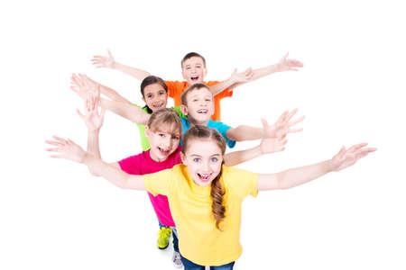 グループでカラフルな t シャツ上げられた手を持つ子どもたちの笑顔に一緒に立っています。トップ ビュー。白で隔離されます。