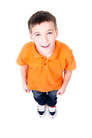 Portrait of adorable young happy boy looking up in orange t-shirt. Top view. Isolated on white background. 免版税图像