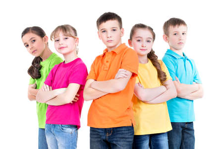 Group of children with crossed arms in colorful t-shirts standing together on white background.