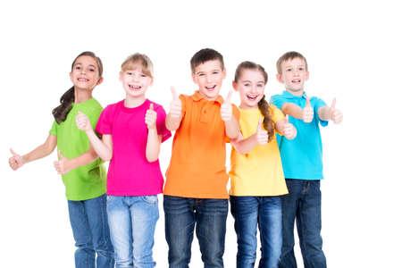 schoolchild: Groep gelukkige jonge geitjes met duim omhoog teken in kleurrijke t-shirts staan samen - geïsoleerd op wit.