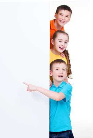 cute young boy: Cheerful group of children pointing on white banner - isolated on white background.