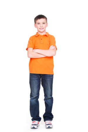 Happy little boy with crossed hands looking at camera in full length standing on white background. Banque d'images